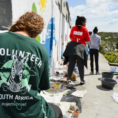 A volunteer paints a mural on a school wall during her volunteer work abroad